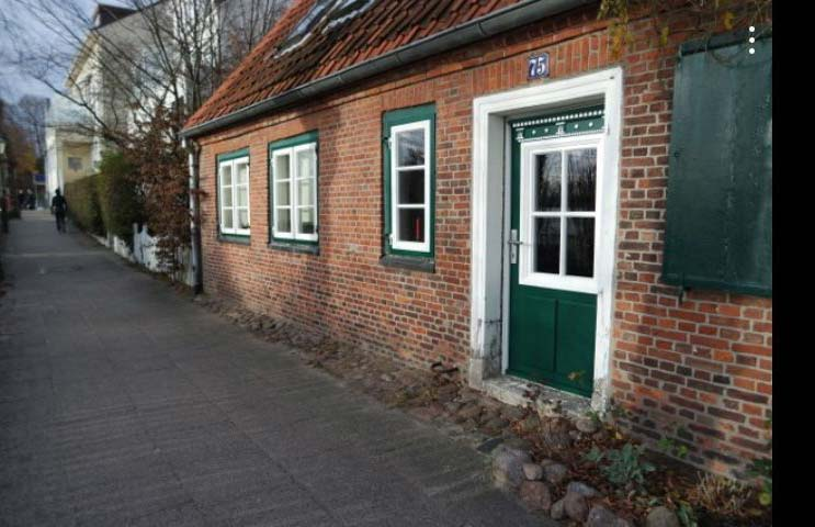 Die grüne Tür mit weißer Verzierung: Nur die Tür mit Zarge wurde erneuert, die Bekleidung blieb alt.